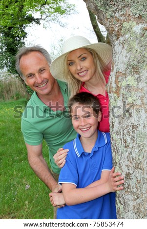 Portrait of happy family standing by a tree - stock photo