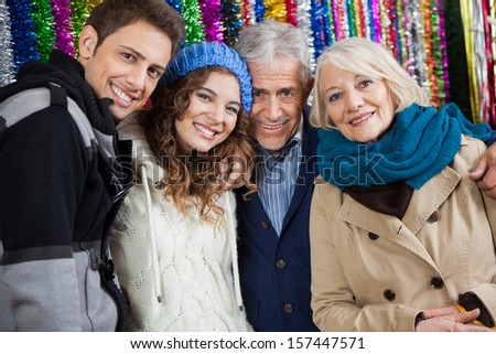 Portrait of happy family standing together against tinsels at store - stock photo