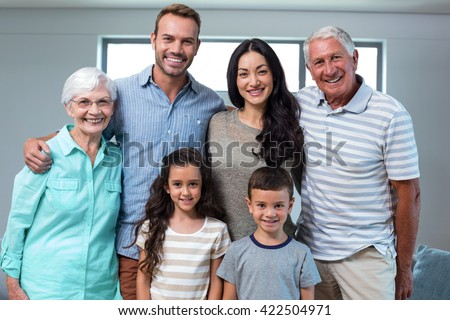 Portrait of happy family standing together and smiling in living room - stock photo