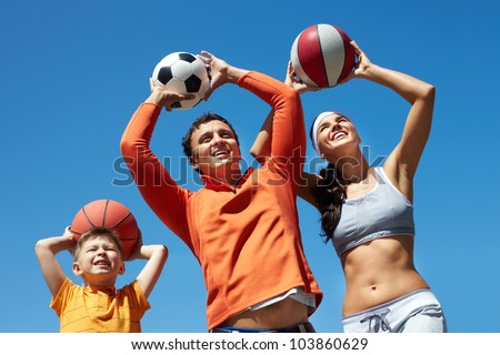 Portrait of happy family throwing balls while playing outside - stock photo