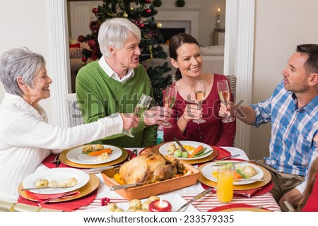 Portrait of happy family toasting at christmas dinner at home in the living room - stock photo