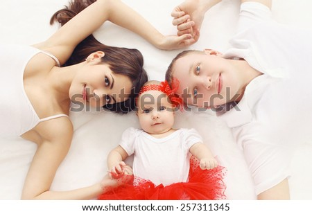 Portrait of happy family together lying on the bed at home, top view - stock photo