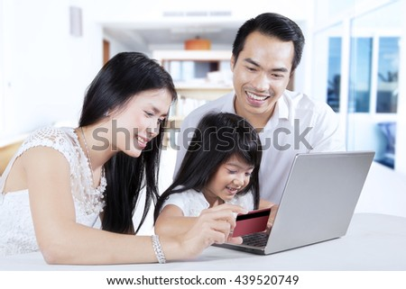Portrait of happy family using laptop computer and credit card for shopping and paying online - stock photo