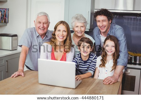 Portrait of happy family using laptop on table in kitchen at home - stock photo