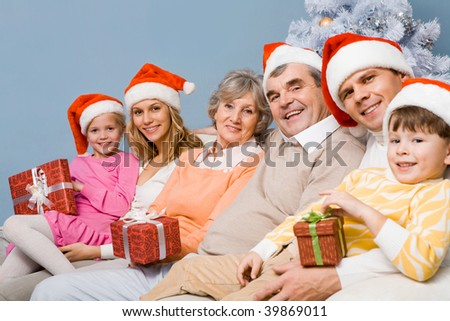 Portrait of happy family wearing Santa caps on Christmas Eve