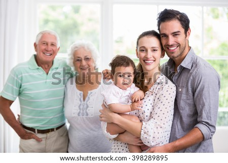 Portrait of happy family with baby at home - stock photo