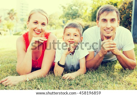 Portrait of happy family with boy in school age lying on green lawn in park. Focus on kid - stock photo