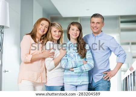 Portrait of happy family with children standing together at home - stock photo