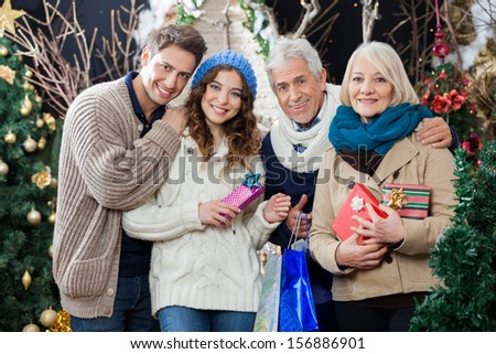 Portrait of happy family with Christmas presents and shopping bags standing in store