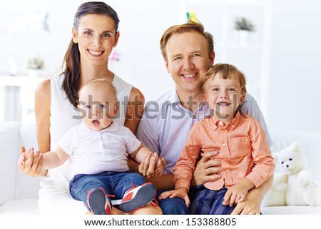 Portrait of happy family with cute sons looking at camera