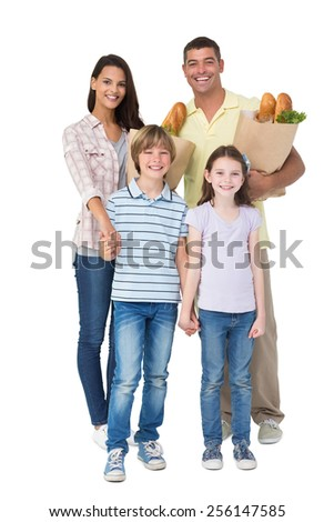 Portrait of happy family with grocery bags over white background - stock photo