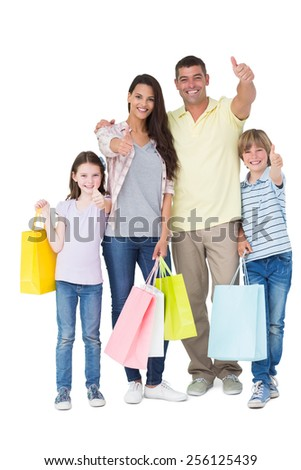 Portrait of happy family with shopping bags gesturing thumbs up over white background - stock photo