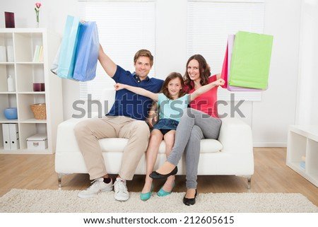 Portrait of happy family with shopping bags relaxing on sofa at home - stock photo