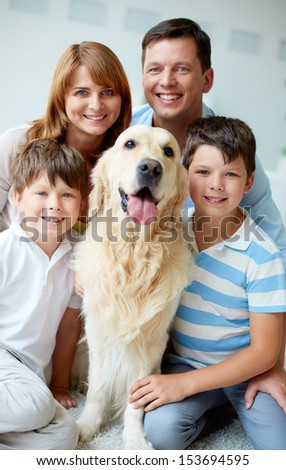 Portrait of happy family with their pet looking at camera - stock photo