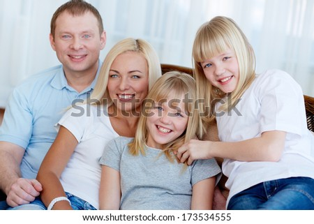 Portrait of happy family with twin daughters smiling at camera
