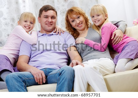 Portrait of happy family with twins sitting on the sofa