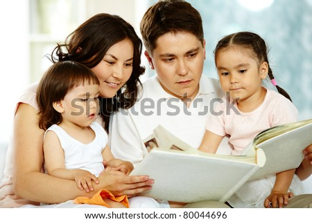 Portrait of happy family with two children reading at home