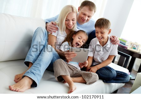 Portrait of happy family with two children sitting on sofa - stock photo