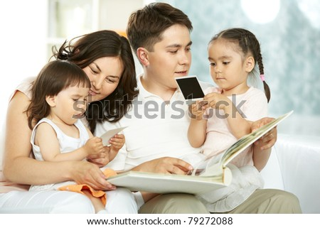 Portrait of happy family with two children spending time at home - stock photo