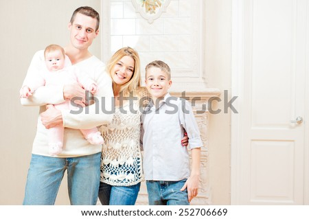 Portrait of happy family with two children, teenage son and baby girl, standing together at home - stock photo