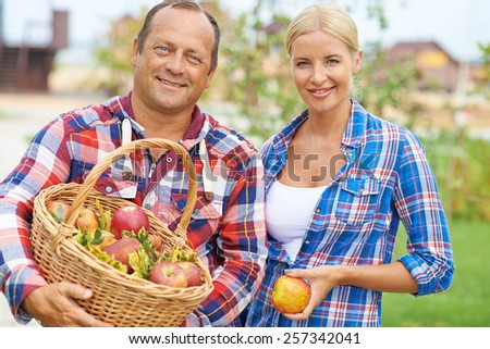 Portrait of happy farmers with fresh apples - stock photo