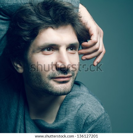 Portrait of happy fashionable handsome mature man in gray sweater (pullover) posing over dark blue (green) background with a friendly smile. Hand on head. Perfect hair and skin. Close up. Studio shot - stock photo