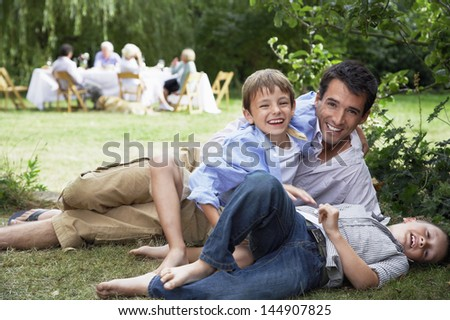 Portrait of happy father and children having fun in grass with family in background - stock photo