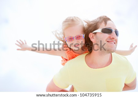 Portrait of happy father and daughter outdoors on summer sunny day - stock photo