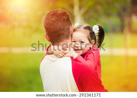 Portrait of happy father and his adorable little daughter. Happy childhood. Beautiful girl of 3 yers hugging her daddy with love. Family life. - stock photo