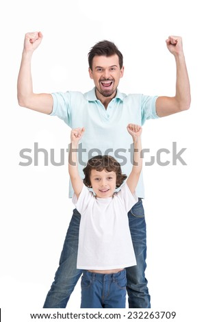 Portrait of happy father and his smiling son, on the white background, raised their hands up. - stock photo