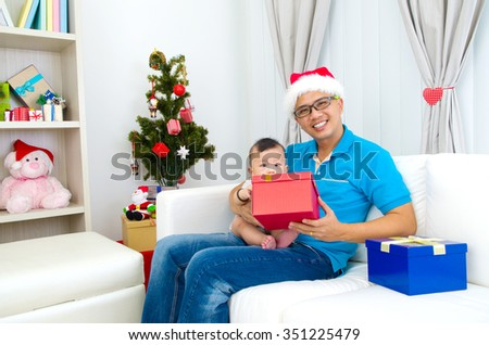 Portrait of happy father and his son in Santa caps on Christmas eve