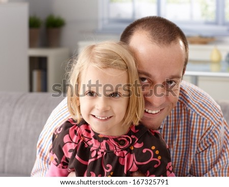 Portrait of happy father and little daughter embracing heads together, laughing, having fun. - stock photo