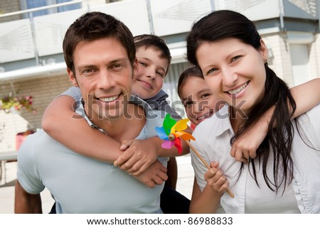 Portrait of happy father and mother enjoying with their kids outdoors - stock photo