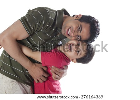 Portrait of happy father and son embracing each other over white background - stock photo