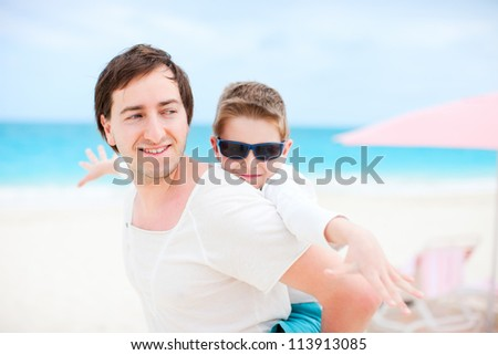 Portrait of happy father and son enjoying time at beach - stock photo