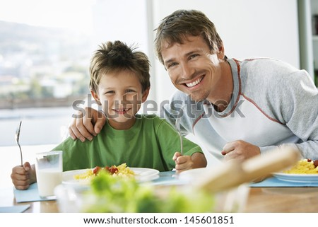 Portrait of happy father and son having breakfast together at dining table - stock photo