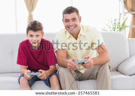 Portrait of happy father and son playing video game on sofa at home