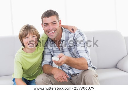 Portrait of happy father and son using remote control on sofa at home - stock photo