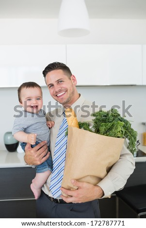Portrait of happy father carrying baby boy and vegetables in kitchen
