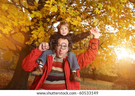 Portrait of happy father giving son piggyback ride on his shoulders in autumn park. - stock photo