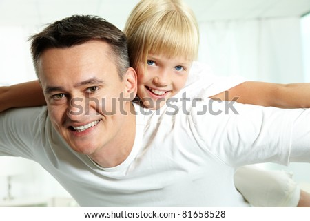 Portrait of happy father holding daughter on back and both looking at camera