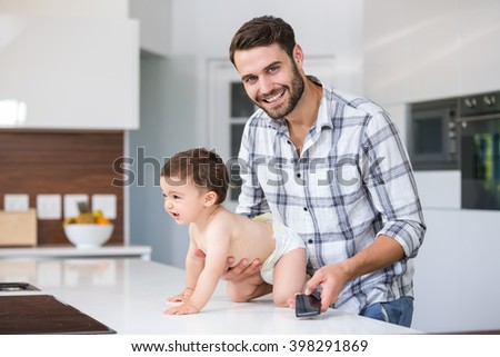 Portrait of happy father holding son at table in house