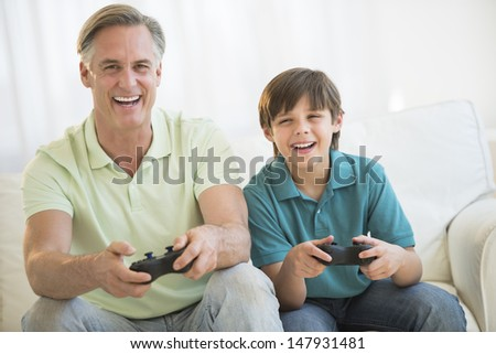 Portrait of happy father playing video game together on sofa at home - stock photo