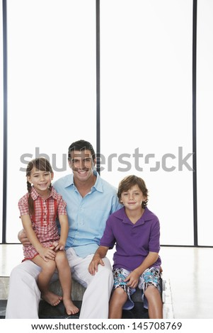 Portrait of happy father with children sitting together at home - stock photo