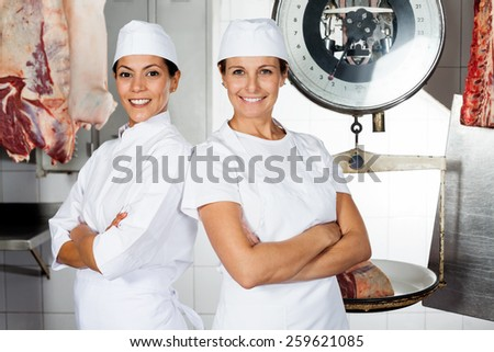 Portrait of happy female butchers standing arms crossed in butchery - stock photo