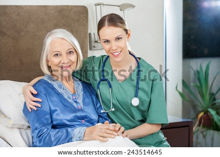 Portrait of happy female caretaker with arm around senior woman at nursing home - stock photo