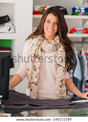 Portrait Of Happy Female Cashier At Counter In Supermarket - stock photo