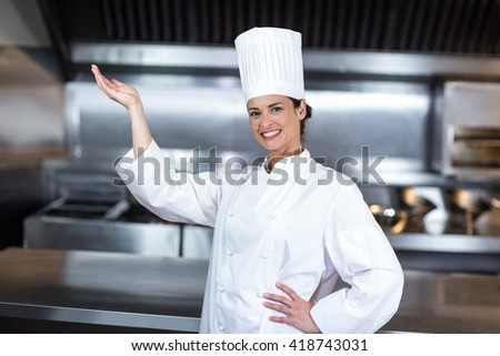 Portrait of happy female chef gesturing while standing in commercial kitchen - stock photo