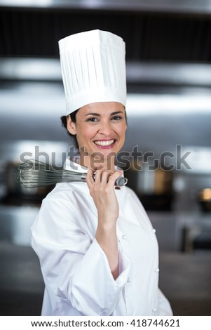 Portrait of happy female chef holding wire whisk in commercial kitchen - stock photo