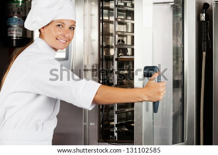 Portrait of happy female chef opening oven door at commercial kitchen - stock photo